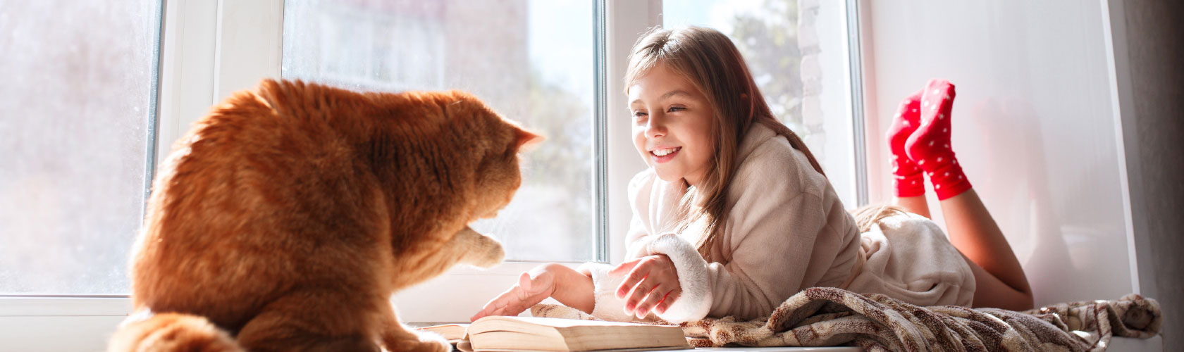 small girl in a robe and red socks looking at an orange cat licking its paws